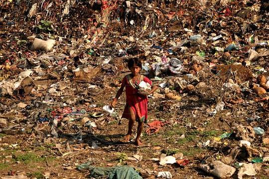 Một đứa trẻ lục lọi trong đống rác ở thủ đô Dhaka - Bangladesh. Ảnh: Photosbangladesh
