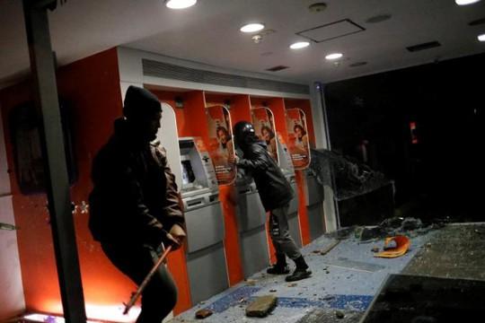 Người biểu tình đập phá ATM. Ảnh: Reuters