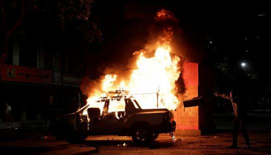 Hình ảnh một chiếc xe hơi bị thiêu cháy trong cuộc biểu tình. Ảnh: Reuters