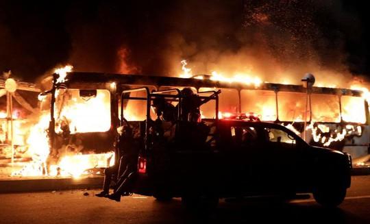 Ít nhất 8 xe buýt bị thiêu rụi trong cuộc biểu tình ngày 28-4. Ảnh: Reuters