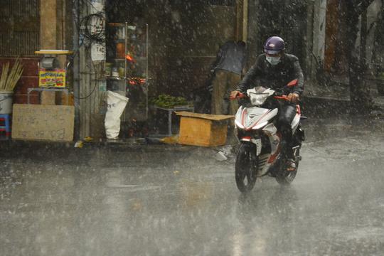 Trưa 16-3 mưa trái mùa bất ngờ khiến người dân ở TP HCM không kịp mặc áo mưa.