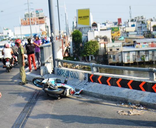 Chiếc xe máy của nạn nhân nằm chỏng chơ trên cầu Nguyễn Văn Cừ