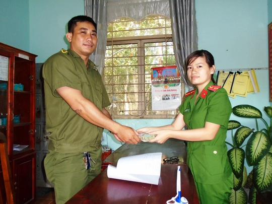 Nữ thiếu úy Nguyễn Thị Phương Thảo (bìa phải) bàn giao số tiền cho công an xã cất giữ chờ người làm rơi đến nhận (Ảnh Hoài Phương)