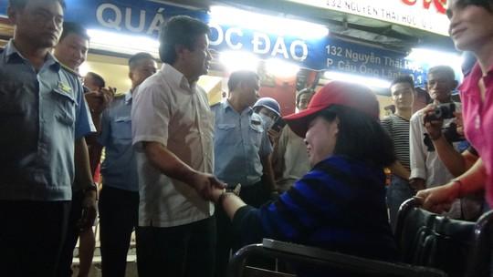 PCT quận 1 Đoàn Ngọc Hải bắt tay, hỏi thăm 1 người phụ nữ khuyết tật khi làm nhiệm vụ.