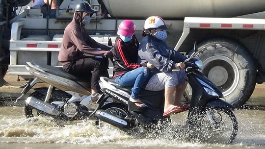 Người đi xe máy khó khăn khi lưu thông qua vùng nước ngập