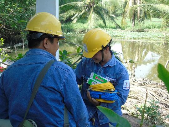 Nhân viên công ty Điện lực Bình Chánh mang thiết bị điện đến tận nhà người dân tại ấp 4, xã Tân Nhựt, huyện Bình Chánh để lắp miễn phí