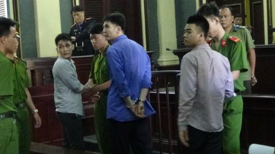Ba bị cáo ngoái lại nhìn người thân sau khi nghe tuyên án, bị áp giải lên xe tù.