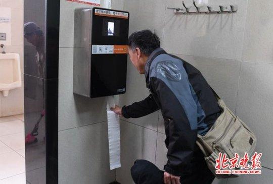 Một người đang lấy giấy vệ sinh từ chiếc máy thông minh có camera nhận diện khuông mặt. Ảnh: The Beijinger.