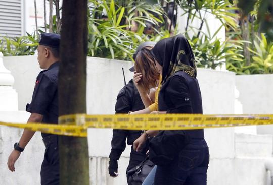 Đoàn Thị Hương (áo vàng) được cảnh sát hộ tống vào tòa án. Ảnh:AP
