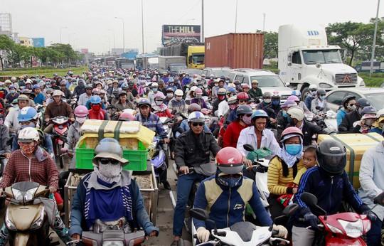 """Qua ghi nhận của phóng viên, đoạn Quốc lộ 1 kéo dài từ vòng xoay An Lạc (quận Bình Tân) đến cầu Bình Điền (huyện Bình Chánh), các loại xe xếp ken đặc mặt đường. Hàng ngàn người đi xe máy kèn cựa nhau, nhích từng chút để lưu thông, trong khi dòng ô tô cũng như """"chôn chân"""" trên mặt đường"""