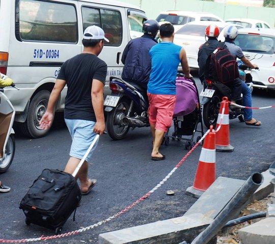 Nhiều người phải kéo hành lý đi bộ vào sân bay do sợ trễ giờ vì kẹt xe