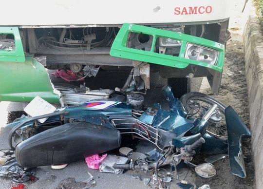 Chiếc xe máy kẹt cứng dưới gầm xe buýt trong tình trạng biến dạng hoàn toàn. Còn xe buýt cũng vỡ nát phần đầu sau cú tông