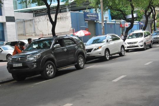 Trước số nhà 92-94 Nguyễn Du, xe ô tô đậu thành hàng nối dài dưới lòng đường. Nhiều người nghi ngờ khu vực này có tình trạng bảo kê bởi nơi đây cấm đậu xe.