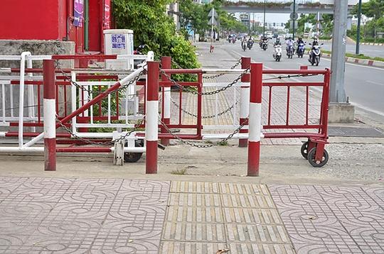 Nhân viên gác chắn đường sắt không đẩy hết rào chắn vào trong mà vẫn để lấn vỉa hè