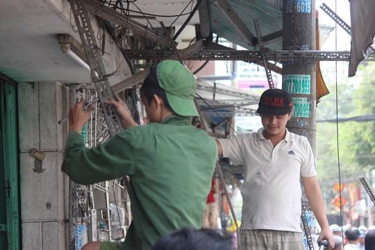 Người dân tự giác tháo dỡ đồ đạc lấn chiếm vỉa hè Ảnh: Quốc Chiến