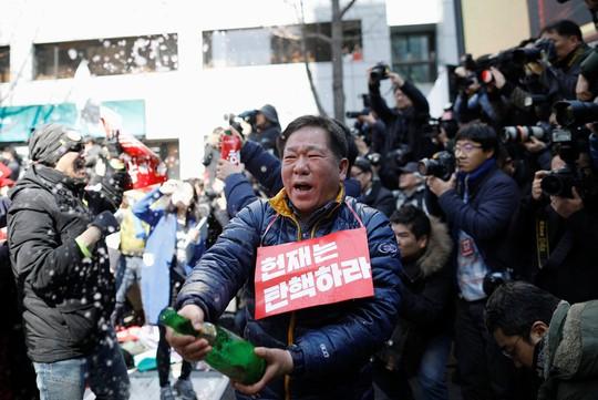 Nhiều người vui mừng mở sâm-panh ăn mừng. Ảnh: Reuters