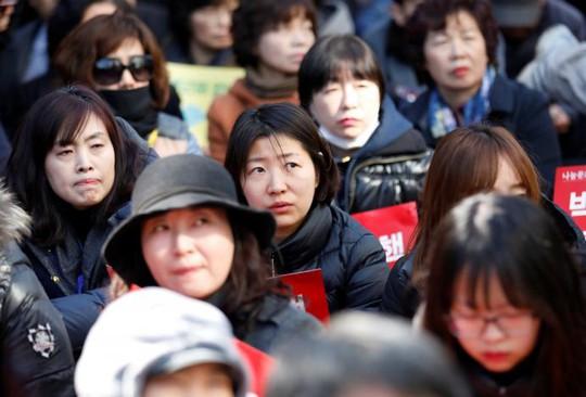 Người dân chăm chú lắng nghe phán quyết bên ngoài Tòa án Hiến pháp. Ảnh: Reuters