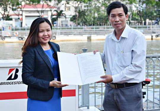 Chị Dương An Giang - Tổng quản lý cấp cao Bridgestone Việt Nam bàn giao xe đạp lọc nước cho Trưởng ban quản lý đường hầm sông Sài Gòn