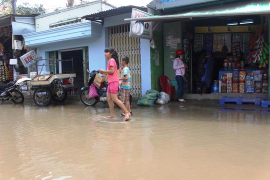 Tiệp tạp hóa của chị Nguyễn Thị Phượng phải đắp đê, cạnh nhà bà Phượng tiệm kem, rồi đến tiệm uốn tóc phải dọn đi nơi khác vì ngập úng