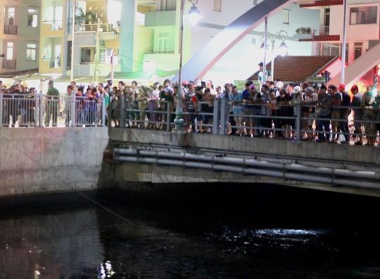Nhiều người đứng kín bên bờ lênh Tân Hóa - Lò Gốm theo dõi việc lặn tìm nạn nhân của lực lượng chức năng