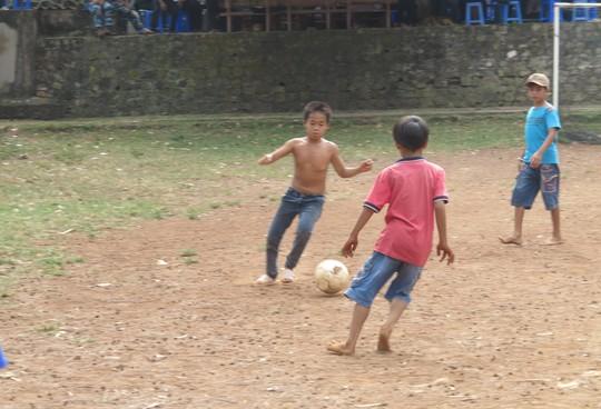 Một số đứa trẻ vượt dốc lên sân bóng của trạm biên phòng để thỏa sức vui chơi.