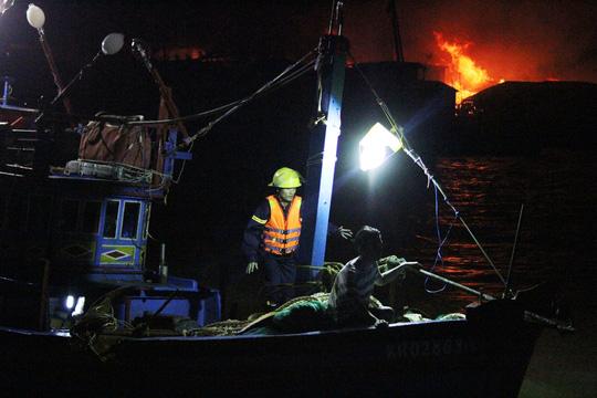 Lực lượng chức năng lên thuyên của người dân để dập lửa