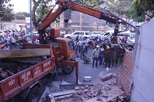 Máy múc được điều động kéo dỡ bức tường kiên cố còn lại.