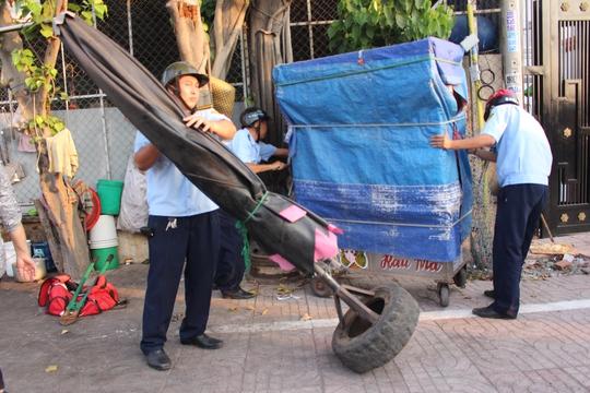 Phát hiện một xe bánh mì cùng nhiều đồ đạc để trên vỉa hè Kinh Dương Vương lấn chiếm vỉa hè, ông Bình chỉ đạo cắt khóa, đưa lên xe chuyên dụng.