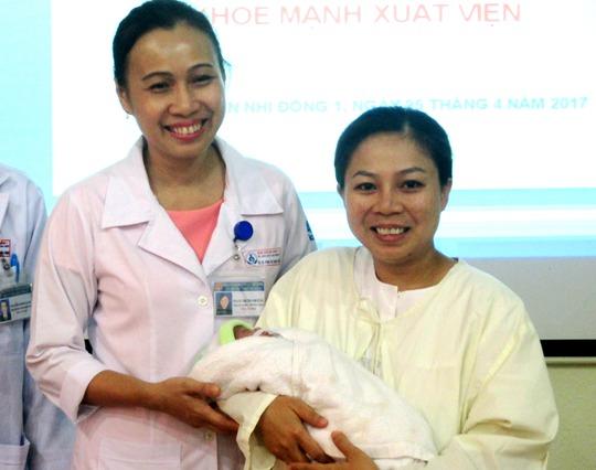 Chị Trương Thị Hoa Mỹ (phải) hết sức vui mừng khi con được xuất viện
