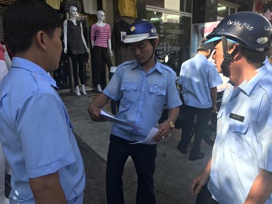 Lực lượng chức năng quận Tân Phú phát phiếu cam kết cho từng hộ dân đề nghị họ thực hiện nghiêm việc bảo đảm đường thông, hè thoáng.