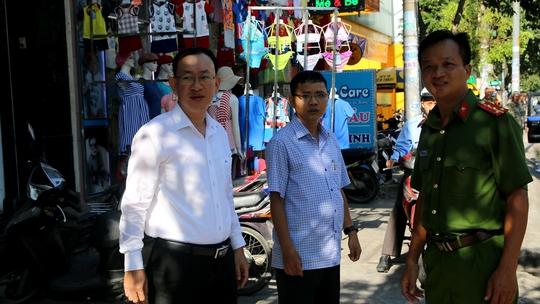Ông Nguyễn Quốc Thái, Phó Chủ tịch UBND quận Tân Phú (trái), cùng lực lượng chức năng xuống đường kiểm tra tình hình lấn chiếm lòng lề đường Nguyễn Sơn sáng 28-2.