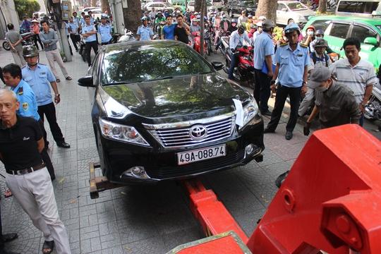 Một chiếc xe Camry đậu trên vỉa hè đường Tôn Đức Thắng bị cẩu về trụ sở cơ quan chức năng.
