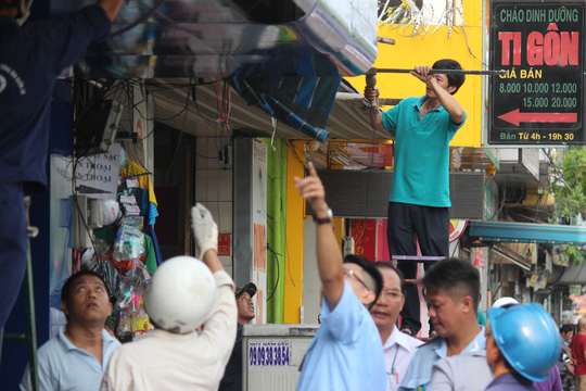 Dân tự nguyện tháo bỏ phần biển hiệu lấn chiếm vỉa hè.