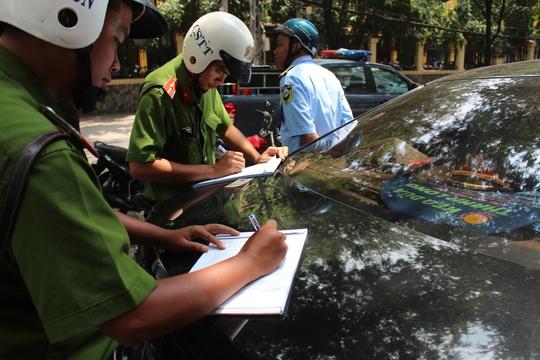 Xe vi phạm lấn chiếm vỉa hè có để quân phục ngành trên xe.