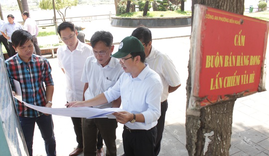 Chủ tịch quận 1 xem xét bản vẽ của đề án xây dựng phố Hàng Rong tại công viên Bạch Đằng.