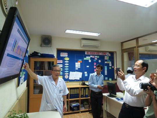 TS-BS Nguyễn Thanh Hùng (trái) đang phân tích bảng theo dõi tại Phòng Quản lý chất lượng của Bệnh viện Nhi Đồng 1
