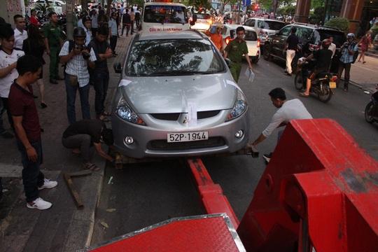 Một chiếc xe đậu dưới lòng đường Hải Triều bị cẩu về trụ sở cơ quan chức năng.