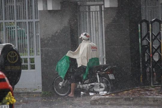 Mưa kèm gió mạnh khiến nhiều người có áo mưa cũng phải ghé vào trú ẩn.