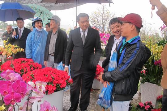 Chủ tịch Huỳnh Đức Thơ cùng Phó chủ tịch Đặng Việt Dũng hỏi thăm một người bán hoa tại chợ hoa Tết Đà Nẵng trong sáng 25-1