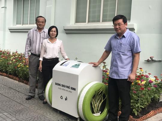 Ông Nguyễn Toàn Thắng, Giám đốc Sở TN-MT TP HCM (phải), trao tặng thùng rác thông minh cho đại diện UBND quận 1 và quận 5.