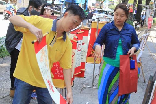 Người dân đến phố ông đồ trước Cung Văn hóa Lao Động mua tranh thư pháp