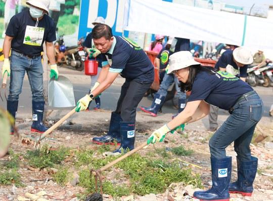 Ông Trần Đoàn Trung, Phó chủ tịch LĐLĐ TP và bà Nguyễn Thị Hoàng Vân, Giám đốc Quỹ CEP đang phát quang cỏ dại ven đường Ngô Sỹ Liên
