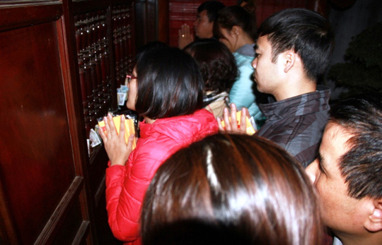 Nhiều người nhét tiền lên cửa, chắp tay khấn vái ngay trước bàn thờ trong cấm cung
