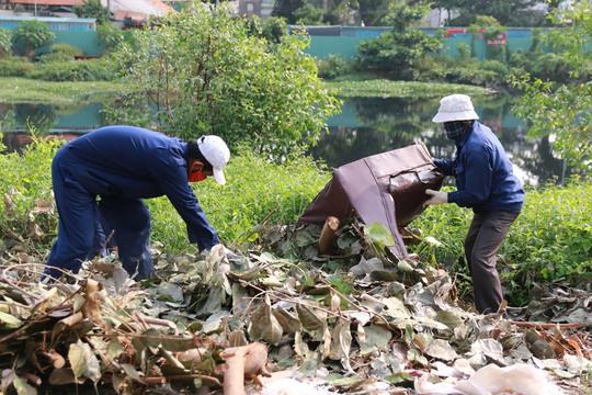 Công nhân Công ty Dịch vụ Công ích quận 8, TP HCM dọn dẹp rác ven kinh