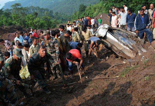 Lực lượng cứu hộ tìm kiếm thi thể trên 2 xe buýt bị lở đất cuốn xuống vực. Ảnh: Reuters