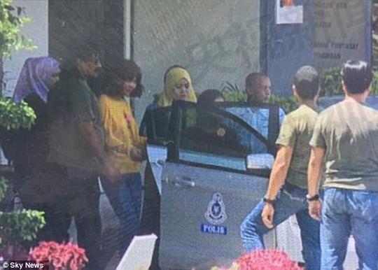Nữ nghi phạm đầu tiên bị bắt (áo vàng). Trong ảnh: Cô này được dẫn giải ra khỏi đồn cảnh sát quận Sepang, bang Selangor - Malaysia vào trưa 16-2. Ảnh: Sky News