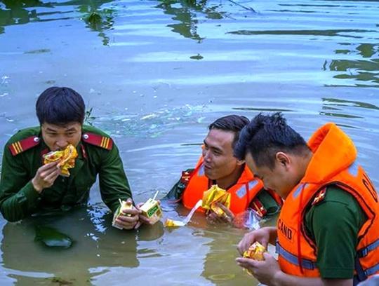 Công an, bộ đội dầm mình trong nước ăn vội, giúp dân chống lũ dữ - Ảnh 12.