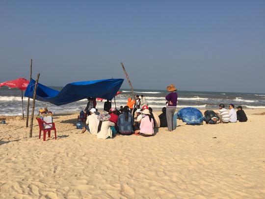 Người dân và bạn bè ngồi đợi tại bãi biển