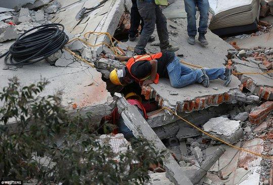 Nhân viên cứu hộ chui vào khe hở tìm người gặp nạn. Ảnh: AP