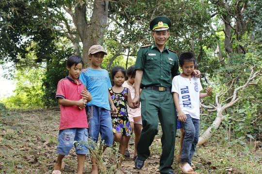 Hằng ngày những đứa trẻ này vượt khoảng 500m đường núi để đến lớp học tình thương. Trong ảnh: Thượng úy Trần Bình Phục, giáo viên duy nhất tại đảo dạy 22 em học sinh. Ngày thường, anh vượt dốc núi xuống đón các em rồi đưa các em trở về.
